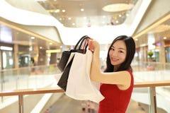 Gelukkige Aziatische Chinese moderne modieuze vrouw het winkelen zakken in een van de de kopersglimlach van de wandelgalerijopsla stock foto