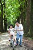 Gelukkige Aziatische familie berijdende fiets Royalty-vrije Stock Afbeelding