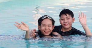 Gelukkige Aziatische familie die spelend samen zwembad bij het park van het waterthema genieten van stock video