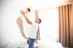Gelukkige Aziatische familie met zoon thuis op slaapkamer het spelen en l Stock Foto