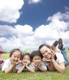 Gelukkige Aziatische familie op het gras Stock Afbeelding
