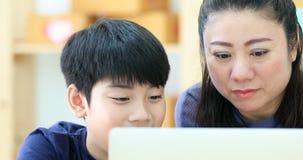 Gelukkige Aziatische familiemoeder en zoons het letten op en lach terwijl het kijken computerlaptop stock video