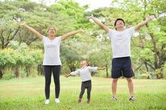 Gelukkige Aziatische familietraining bij het park stock afbeeldingen
