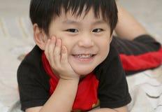 Gelukkige Aziatische jongen die op bed ligt stock fotografie