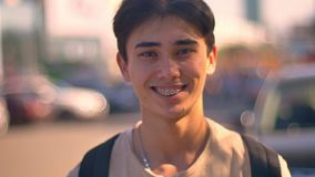 Gelukkige Aziatische kerel bij camera lachen, close-up zich op de straat bevinden, auto's en weg op de achtergrond, het stadsleve stock videobeelden