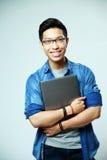 Gelukkige Aziatische mens die zich met laptop bevinden Royalty-vrije Stock Foto's
