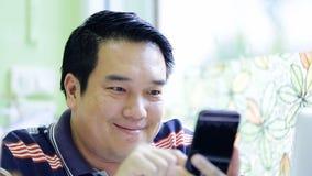 Gelukkige Aziatische mens die zijn slimme telefoon met behulp van stock video