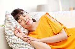 Gelukkige Aziatische tienerslaap op bank thuis Royalty-vrije Stock Foto's