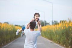 Gelukkige Aziatische vader die zijn jong geitje het spinnen rond met pret houden stock fotografie