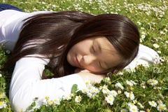 Gelukkige Aziatische vrouw die in grasslaap liggen die in park in de lente rusten royalty-vrije stock foto's