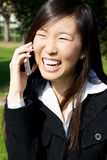 Gelukkige Aziatische vrouw op telefoon het lachen stock afbeelding
