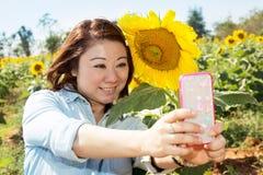Gelukkige Aziatische vrouw selfy met zonbloem op het gebied van de zonnebloembloem Royalty-vrije Stock Foto