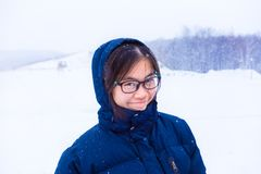 Gelukkige Aziatische vrouwelijke tiener in blauwe de winterjasje statusoutsi Stock Foto