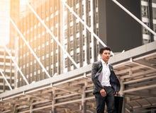 Gelukkige Aziatische zakenman die langs de straat lopen stock foto