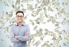 Gelukkige Aziatische zakenman onder de regen van de dollarrekening Royalty-vrije Stock Foto