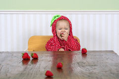 Gelukkige baby die in bessenkostuum aardbeien eten royalty-vrije stock foto