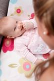 Gelukkige baby die bij het achter glimlachen bij moeder liggen Stock Afbeelding