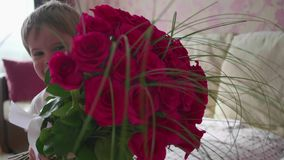 Gelukkige baby die een groot boeket van scharlaken rozen houden Een gift voor moeder` s verjaardag stock videobeelden