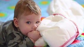 Gelukkige baby die op het bed op zijn maag liggen en met een hoofdkussen spelen Het concept de eerste beweging van jonge geitjes stock footage