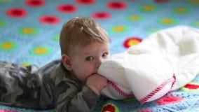 Gelukkige baby die op het bed op zijn maag liggen en met een hoofdkussen spelen Het concept de eerste beweging van jonge geitjes stock video