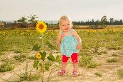 Gelukkige baby die zich naast zonnebloem bevindt royalty-vrije stock foto