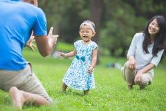 Gelukkige baby die zijn eerste stappen op een groen gras maken stock foto's