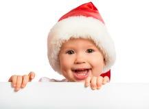 Gelukkige baby in een geïsoleerde Kerstmishoed en een leeg aanplakbord stock fotografie