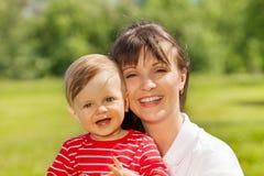 Gelukkige baby en zijn brijzitting in groene weide Stock Fotografie