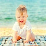 Gelukkige baby op het strand bij de kust Stock Afbeelding