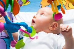 Gelukkige babyjongen in bed met speelgoed Stock Foto