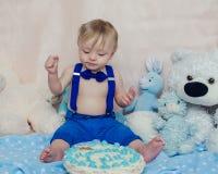 Gelukkige babyjongen die cake voor zijn eerste verjaardagspartij eten Stock Foto's