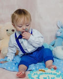 Gelukkige babyjongen die cake voor zijn eerste verjaardagspartij eten stock foto