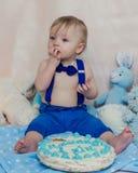 Gelukkige babyjongen die cake voor zijn eerste verjaardagspartij eten Stock Afbeeldingen