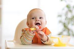Gelukkige babyjongen die op voedsel met lepel bij lijst wachten royalty-vrije stock foto