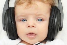 Gelukkige babyjongen in oortelefoons Stock Fotografie