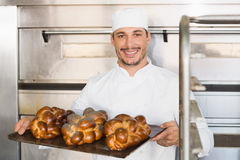 Gelukkige bakker die dienblad van vers brood tonen stock foto