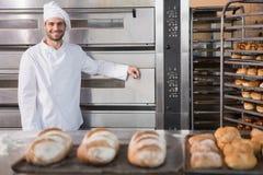 Gelukkige bakker die op professionele oven leunen stock afbeelding