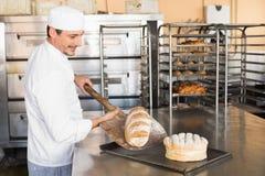 Gelukkige bakker die vers brood nemen royalty-vrije stock foto