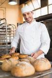 Gelukkige bakker die verse ongezuurde broodjes nemen stock fotografie