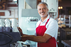 Gelukkige barista die bij camera glimlachen en de koffiemachine met behulp van Stock Fotografie