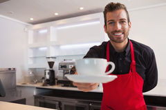 Gelukkige barista die kop van koffie aanbieden aan camera Stock Afbeeldingen