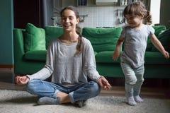 Gelukkige bedachtzame moeder die yoga die met jong geitje doen thuis spelen stock foto