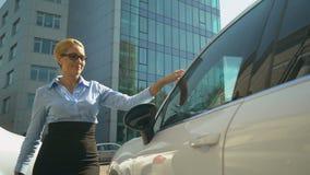 Gelukkige bedrijfsdame die in luxe auto, succesvolle aankoop krijgen, autolening stock footage