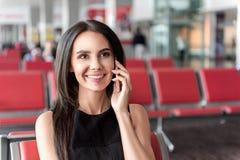 Gelukkige bedrijfsdame die mededeling over telefoon in het wachten zaal hebben Stock Fotografie