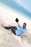 Gelukkige bedrijfsmens die aan het strand met PC werkt royalty-vrije stock afbeelding