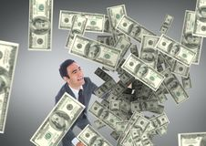 Gelukkige bedrijfsmens die geldregen tegen grijze achtergrond bekijken Royalty-vrije Stock Foto