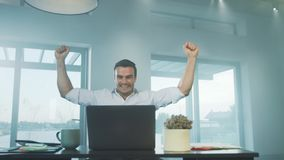 Gelukkige bedrijfsmens die goed nieuws op laptop computer krijgen op het verre werk stock videobeelden