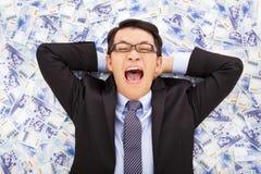 Gelukkige bedrijfsmens die op de stapels van de nieuwe dollar van Taiwan liggen Royalty-vrije Stock Afbeeldingen