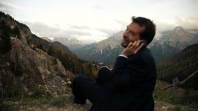 Gelukkige bedrijfsmens die op de telefoon in de berg spreken stock videobeelden