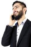 Gelukkige bedrijfsmens die op de telefoon spreken stock afbeelding